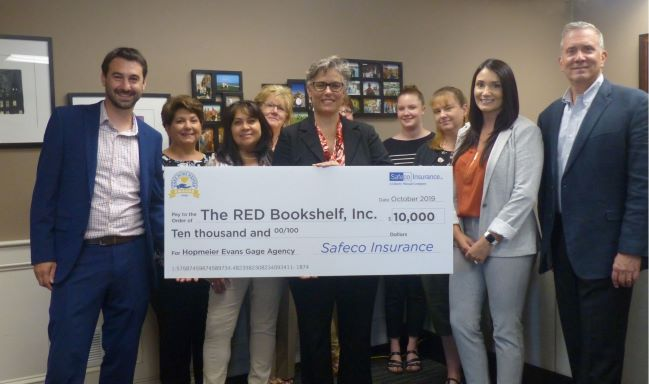 The staff of Hopmeier Evans and Gage Agency pictured with Mary Beth Fowler of The RED Bookshelf along with Daniel MacNeil and Heather Steger of Safeco Insurance